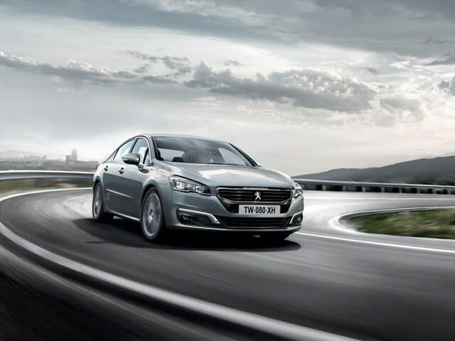 Silver Peugeot 508 in speed drive along a curve road